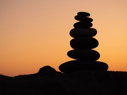cairn at sunset, stones balances, pyramid of stones at sunset, ?oncept of Life balance, harmony and meditation