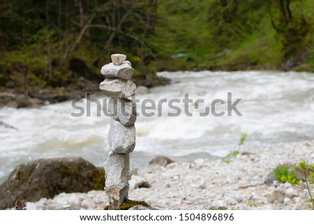 Cairn, stone sculpture, against the mountain river water. White stones of the pyramid in the forest symbolizing zen, harmony, balance.
