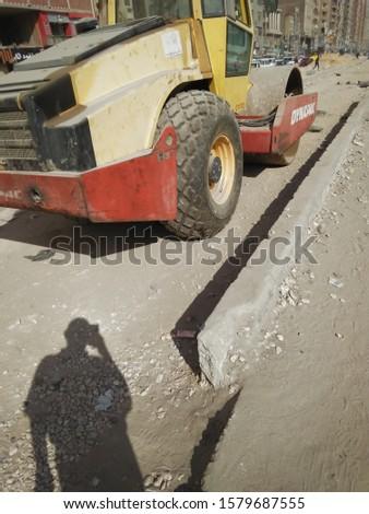 Cairo , Arabic Republic of Egypt - 12.04:2019: tractor prepare the road for asphalting , Cairo city - Egypt #1579687555