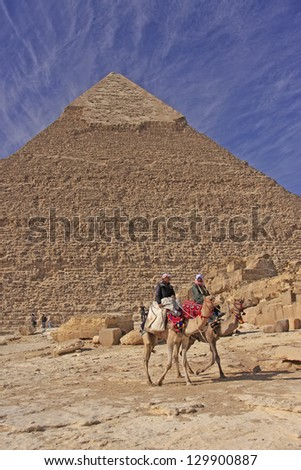 CAIRO, EGYPT - DECEMBER14: Unidentified camel men lead their camels along Pyramid of Khafre on December 14, 2010 in Cairo, Egypt. Pyramid of Khafre is the second largest of ancient Pyramids of Giza.