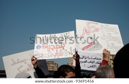CAIRO – JAN 25: Egyptians hold signs calling for the fall of the military council in Cairo, Egypt on January 25, 2012