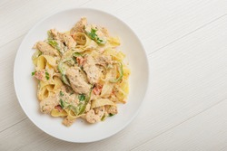 Cajun chicken Fettuccine pasta in a creamy sauce on white plate. Top view.