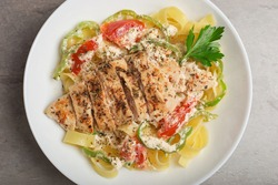 Cajun chicken pasta in a creamy sauce on white plate on stone table. Top view. American cuisine.