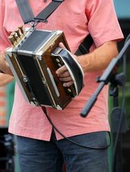 Cajun zydeco musician performing outdoors.