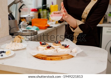 Cake Anna Pavlova. The process of making a cake Anna Pavlova. The pastry chef decorates the cake Anna Pavlova. Making a cake Anna Pavlova. Stock photo ©