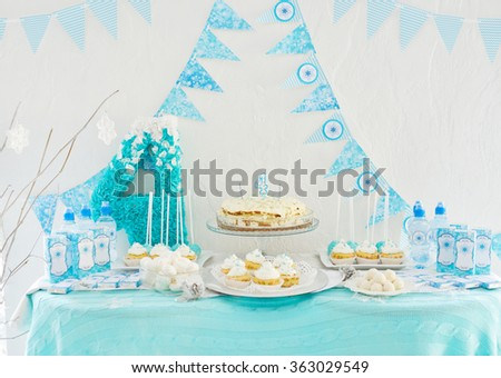 Cake, candies, marshmallows, cakepops for 4th birthday party, focus on candle