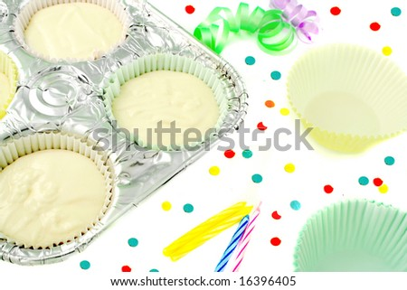cake flour mix in baking pan with tinsel ribbons, candles, confetti, and extra cupcake paper cups on the side