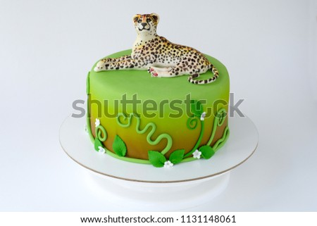 Cake for children's birthday made of green mastic decorated with leopard, flowers, leaves, pattern. Close-up. Cutout. Picture for a menu or a confectionery catalog.