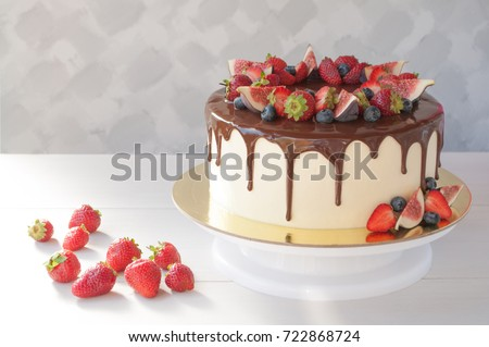 Cake in chocolate, decorated with slices strawberries, blueberries and figs on a white wooden table in the morning sun. Picture for a menu or a confectionery catalog.