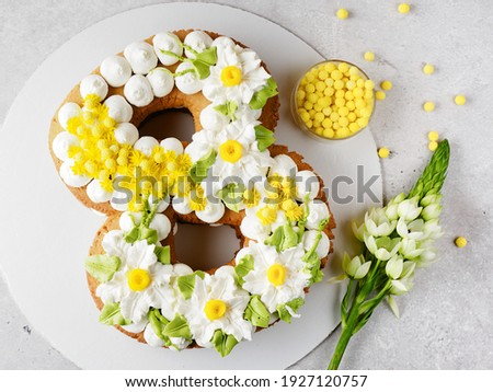 Cake in the form of the number eight for the spring festival. March 8. A cake with a cream decor of daffodils and mimosa. Spring sun on the cake. Dessert and flowers on a gray. Space for text.