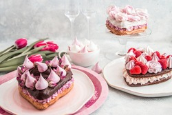 Cake in the shape of a heart from Traditional French dessert eclair and Pavlov cookies on a white background with tulips and glass glasses. Wedding day concept