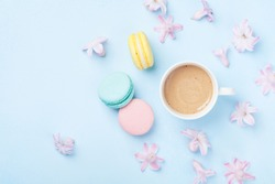 Cake macaron or macaroon, pink flowers and coffee on blue pastel background top view. Creative and fashion composition. Flat lay style.