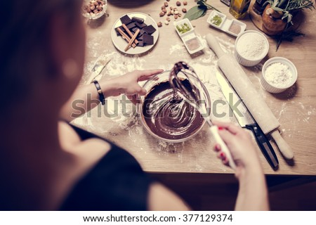 Stock Photo Cake making, preparation.Preparations for making homemade chocolate.Mixed ingredients prepared for baking cake or bake.A whisk in a round bowl with liquid chocolate.Housewife making a chocolate cake