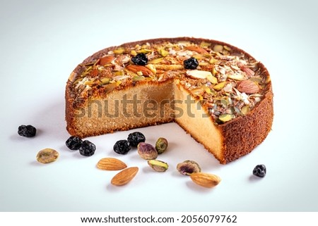 Cake Mawa Cake is a rich, delicious cake made with mawa and atta. Isolated on white background with dry fruit nuts. Homemade round half cut sponge cake. Almond, Cashew, Blackberry, Pistachio.