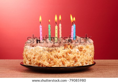 Cake with candles on red background