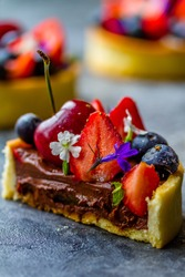 cake with fresh strawberry fruit, bilberry, cherry on a gray background