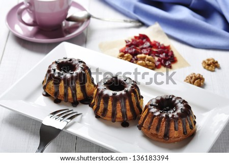 Cake with melted chocolate icing on white dish on wooden background