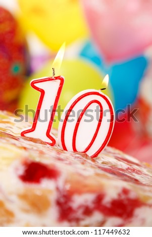 Cake with number 10 candles, on balloons background.