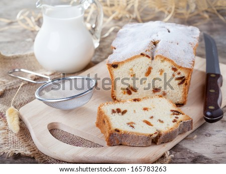 Cake with raisins, sprinkled with powdered sugar and a jug of milk on a wooden table, selective focus on piece of cake