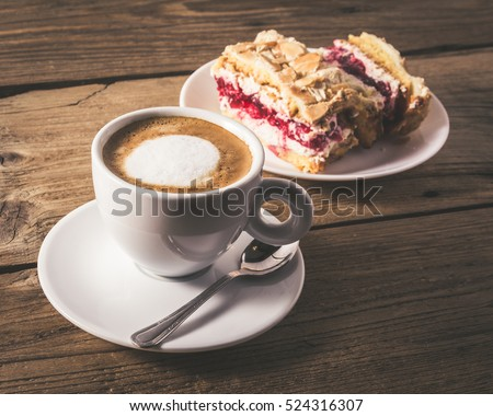 cake with raspberries and cup of coffee on a wooden table #524316307