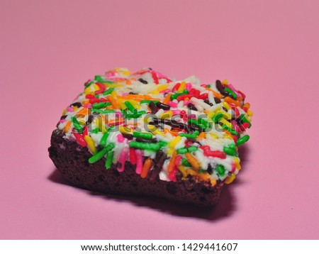 Cake with topping colorful chocolate granules isolated on pink background