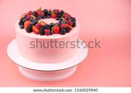 Cake with whipped pink cream, fresh strawberries, blueberries, blackberry and raspberry on pink background. Picture for a menu or a confectionery catalog.