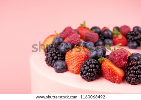 Cake with whipped pink cream, fresh strawberries, blueberries, blackberry and raspberry on pink background. Close up. Picture for a menu or a confectionery catalog.