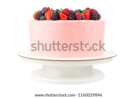 Cake with whipped pink cream, fresh strawberries, blueberries, blackberry and raspberry on white background. Isolated. Picture for a menu or a confectionery catalog.