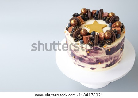 Cake with white and black cream, decorated with blueberries, blackberry, chocolate chip cookies, candies, bars and  gold star on a gray background. Picture for a menu or a confectionery catalog.