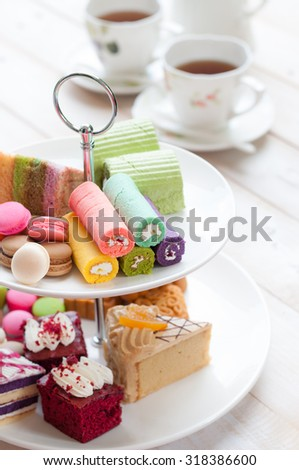 cakes and macaroons on two tiered tray with teapot and cup background. Afternoon tea #318386600