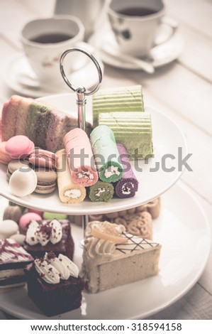 cakes and macaroons on two tiered tray with teapot and cup background. Afternoon tea #318594158