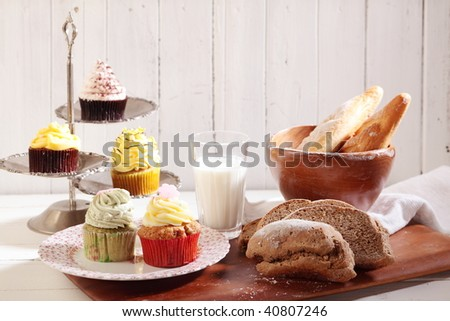 cakes and whole wheat bread, baguette and milk are on the table.