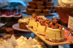 Cakes on display in the Ottolenghi restaurant and shop in Spitalfields, London UK. These are mini cheesecakes with salted caramel nut topping.