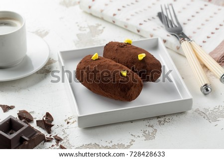 Cakes Rum ball in a white plate on a light background with black coffee and chocolate.