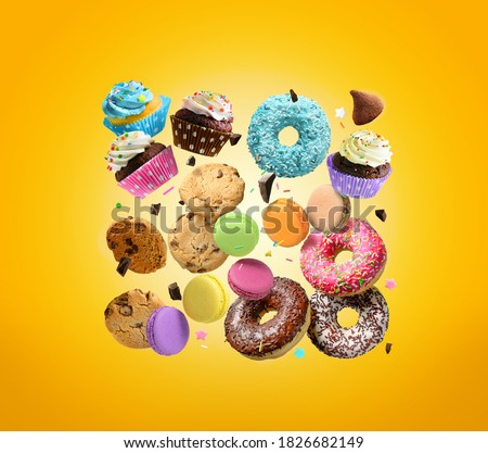 Cakes, sweets, confectionery background. Donuts, cookies cupcakes macaroons flying over yellow background