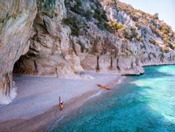Cala Luna Sardinia, young couple with kayak boat on the beach of Cala Luna Sardinia Italy