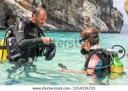 Cala Mariolu, Italy - 28 June 2013: Child discover scuba diving at Cala Mariolu beach on Sardinia, Italy #1254326725