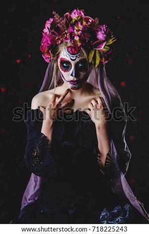 Stock Photo Calavera Catrina in black dress over dark background. Sugar skull makeup. Dia de los muertos. Day of The Dead. Halloween.
