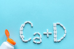 Calcium and Vitamin D Generic Tablets. White pills forming shape to Ca+D alphabet on blue background, copy space, top view.