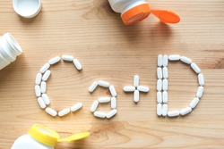 Calcium and Vitamin D Generic Tablets. White pills forming shape to Ca+D alphabet on wooden background, copy space, top view.