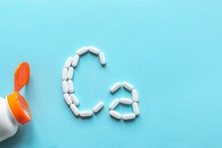 Calcium Tablets. White pills forming shape to Ca alphabet on blue background, copy space, top view.