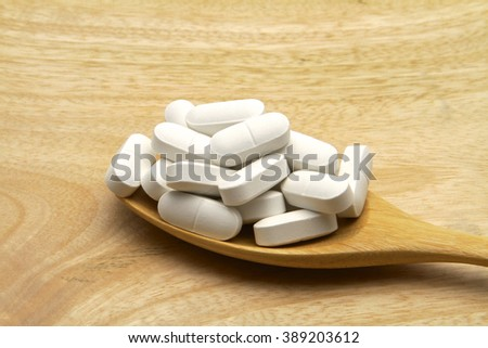 Calcium, vitamin for healthy body on a wooden spoon.