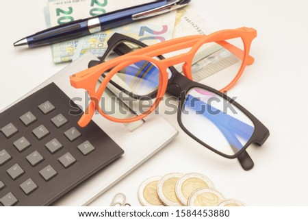 Calculate the money and interest helped by a calculator and a good prescription glasses; Money and papers and clips on the table. Bank interest, finance, calculations