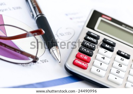 Calculating numbers for income tax return with glasses pen and calculator