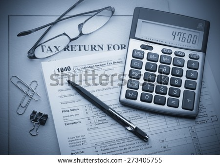 Calculating numbers for income tax return with pen, glasses and calculator