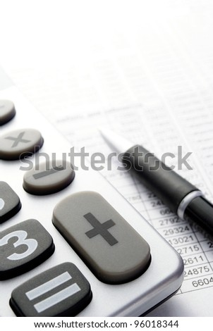 calculator, a pen and paper with numbers on the table