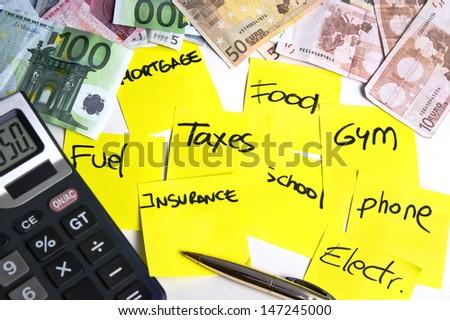 Calculator and banknotes on a table filled with yellow post it notes regarding cost of living: mortgage, taxes, fuel, food, school, phone, insurance, gym and electricity