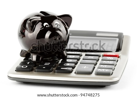 Calculator and black closeup piggy bank on white background