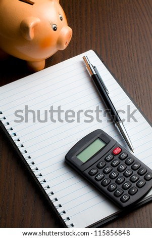 calculator and blank notebook on table