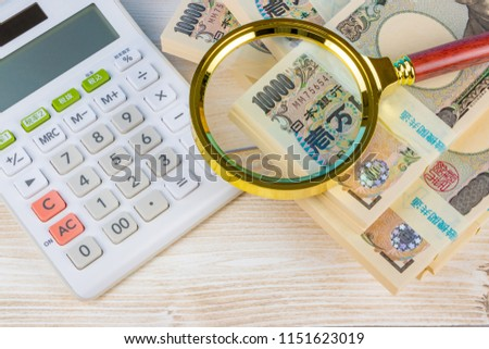 """calculator and cash. Translation on bill text:""""Bank of Japan Tickets""""""""One hundred thousand yen""""""""The Bank of Japan"""" On calculator text:""""Tax rate""""""""Tax exclusion""""""""Tax included""""""""Tax rate setting""""."""